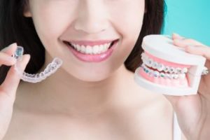 Woman holding an Invisalign tray in one hand and braces in the other