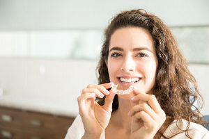 Woman holding a clear aligner for Invisalign.
