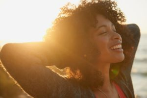 woman relaxing and smiling in the sunset