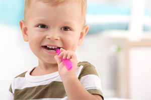 A little boy wearing a striped shirt and using a manual toothbrush to clean his teeth