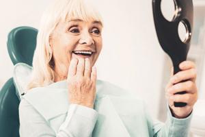 Woman admiring her new dental implants in West Brookfield