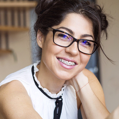 Closeup of woman smiling with traditional orthodontics