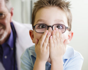 Boy covers his mouth after learning about gum disease in kids